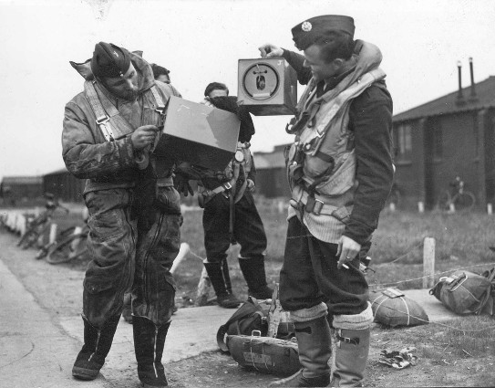 Shows two of the crew of an Australian Lancaster Squadron with their pigeons before leaving for a raid on Berlin